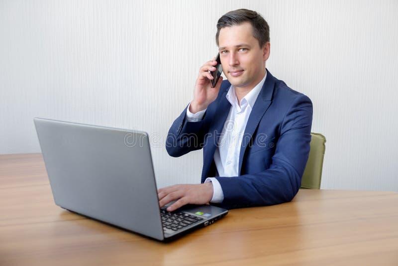 I giovani bei hanno concentrato l'uomo attraente che utilizza il cellulare mentre lavoravano con il computer portatile nell'uffic immagine stock
