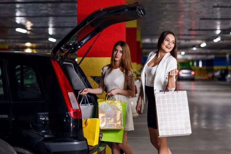 I giovani clienti hanno messo gli acquisti nell'automobile fotografie stock libere da diritti