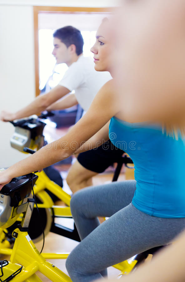 I giovani con forma fisica vanno in bicicletta nella palestra fotografia stock