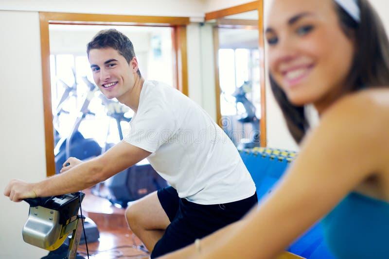 I giovani con forma fisica vanno in bicicletta nella palestra immagini stock libere da diritti