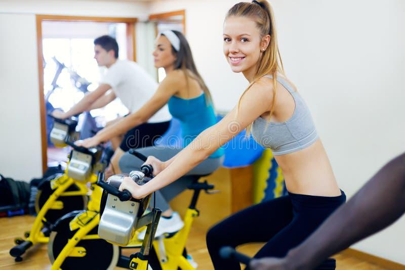I giovani con forma fisica vanno in bicicletta nella palestra immagine stock