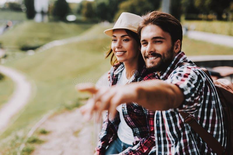 I giovani coppia la seduta sul bordo e l'esame del parco immagini stock libere da diritti