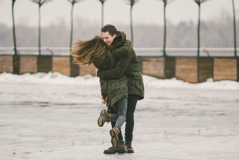 I giovani delle coppie eterosessuali negli studenti di amore un uomo e una donna caucasica Nell'inverno, nel quadrato di città co immagini stock libere da diritti