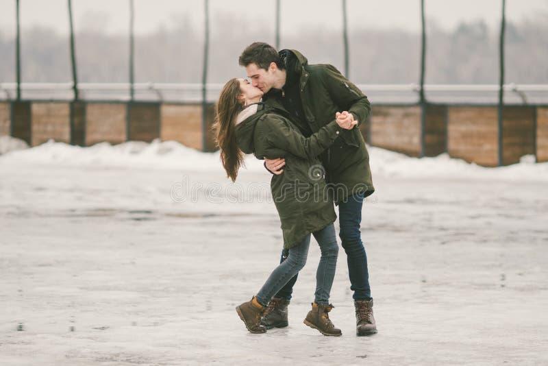 I giovani delle coppie eterosessuali negli studenti di amore un uomo e una donna caucasica Nell'inverno, nel quadrato di città co immagine stock