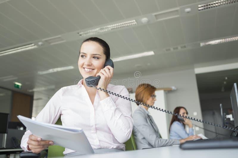 I giovani documenti sorridenti della tenuta della donna di affari mentre usando la linea terrestre telefonano con i colleghi nel  fotografia stock libera da diritti