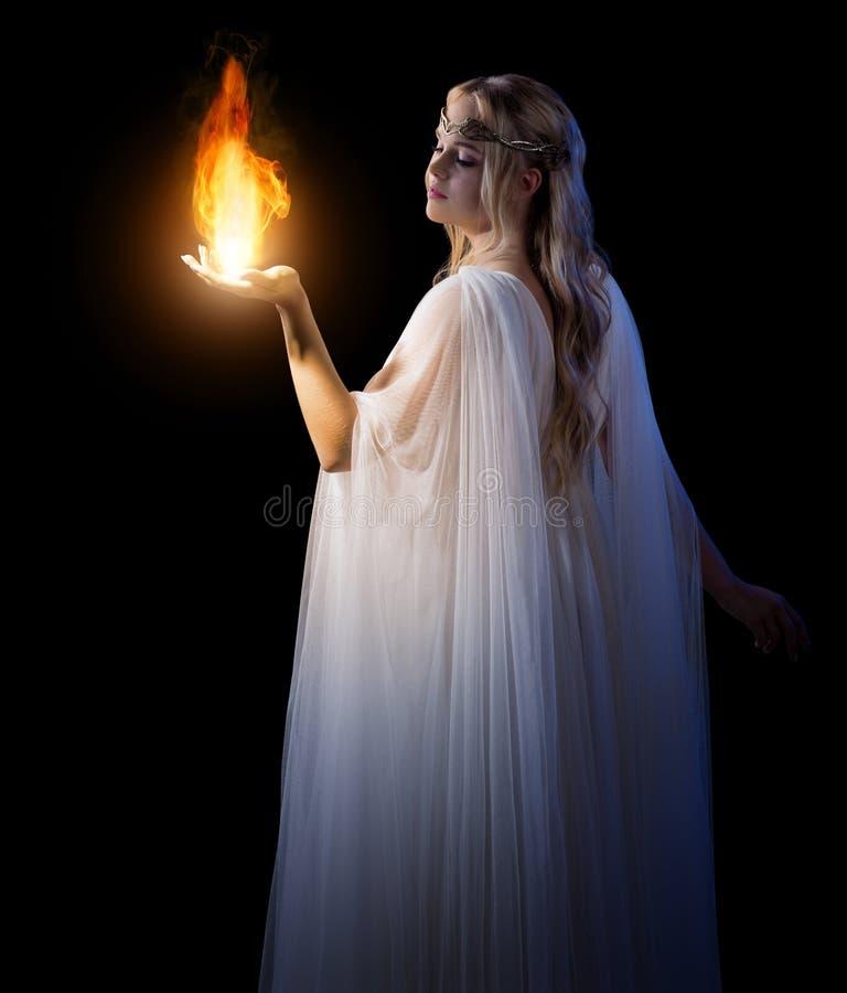 I giovani elven il fuoco di tenuta della ragazza in palme immagini stock