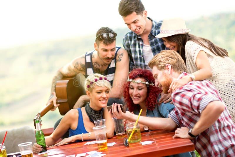 I giovani forniscono lo sguardo alle foto dal picnic al telefono cellulare dei tipi fotografie stock libere da diritti