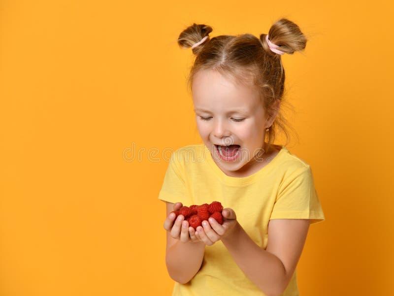 I giovani frutti di bacche della tenuta del bambino della neonata in mani hanno sorpreso i grida di risata felici sul giallo fotografia stock libera da diritti