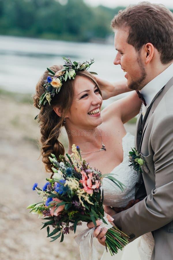I giovani governano e sposa che sta abbracciante sui precedenti del fiume fotografia stock