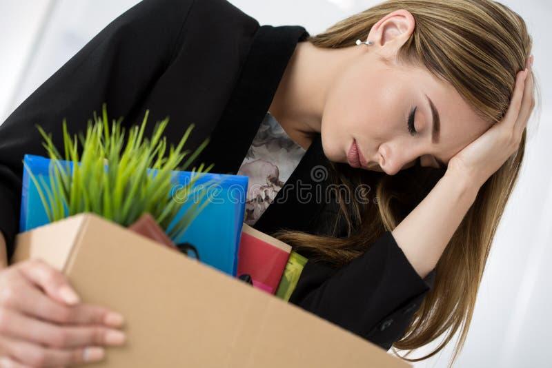 I giovani hanno allontanato la lavoratrice in contenitore di cartone della tenuta dell'ufficio con immagine stock