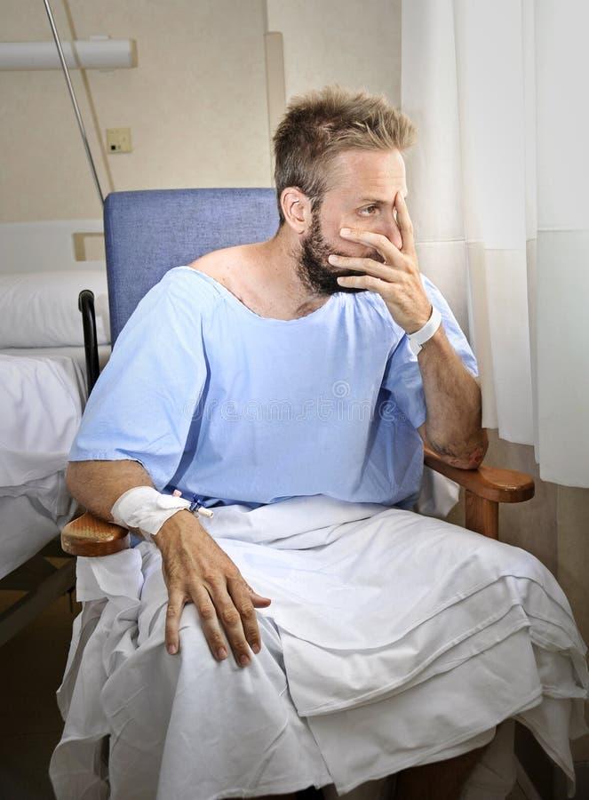 I giovani hanno danneggiato l'uomo nella stanza di ospedale che si siede da solo nel dolore preoccupato per il suo stato di salut immagini stock libere da diritti
