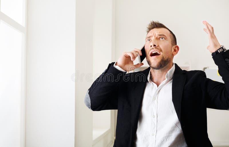 I giovani hanno sollecitato il telefono cellulare di chiamata dell'uomo d'affari in ufficio moderno fotografia stock