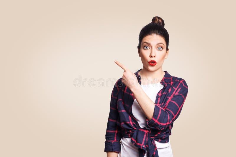 I giovani hanno sorpreso la ragazza con i capelli del panino e di stile casuale che indica il suo dito lateralmente immagine stock libera da diritti