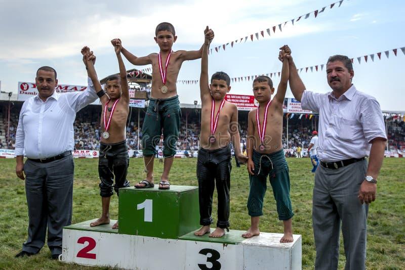 I giovani lottatori stanno sulla pedana al festival lottante dell'olio turco di Elmali, Turchia dei vincitori immagini stock