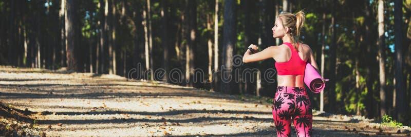 I giovani misura la donna atletica in una foresta che indossa l'orologio astuto e che tiene la stuoia di yoga, camminante a parti fotografie stock libere da diritti