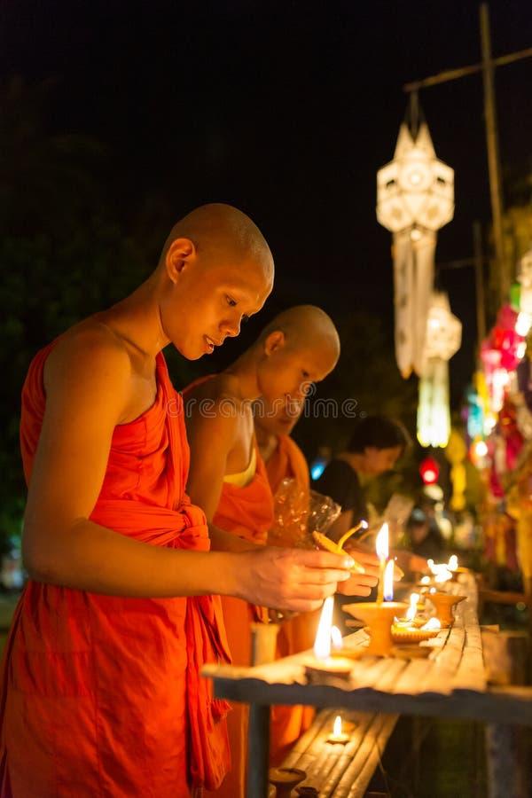 I giovani monaci buddisti infornano le candele al Buddha in Wat Phan Tao Temple durante Yi Peng Festival in Tailandia fotografie stock libere da diritti