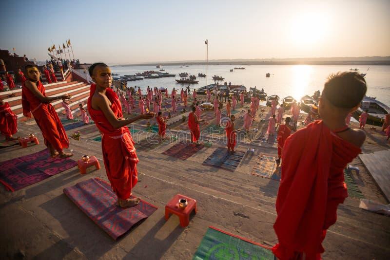 I giovani monaci indù conducono una cerimonia per incontrare l'alba sulle banche di Gange ed alzano la bandiera indiana immagini stock libere da diritti