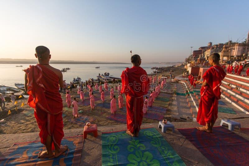 I giovani monaci indù conducono una cerimonia per incontrare l'alba sulle banche di Gange ed alzano la bandiera indiana immagini stock