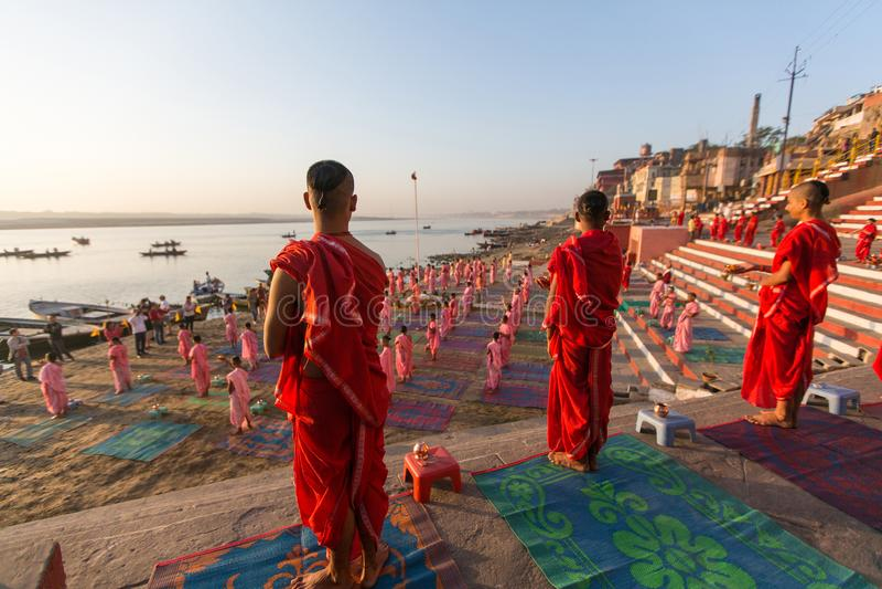 I giovani monaci indù conducono una cerimonia per incontrare l'alba sulle banche di Gange ed alzano la bandiera indiana fotografie stock