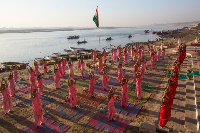 I giovani monaci indù conducono una cerimonia per incontrare l'alba sulle banche di Gange ed alzano la bandiera indiana fotografie stock libere da diritti