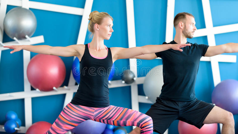 I giovani nella classe di yoga in guerriero posano Concetto del gruppo di yoga fotografia stock libera da diritti