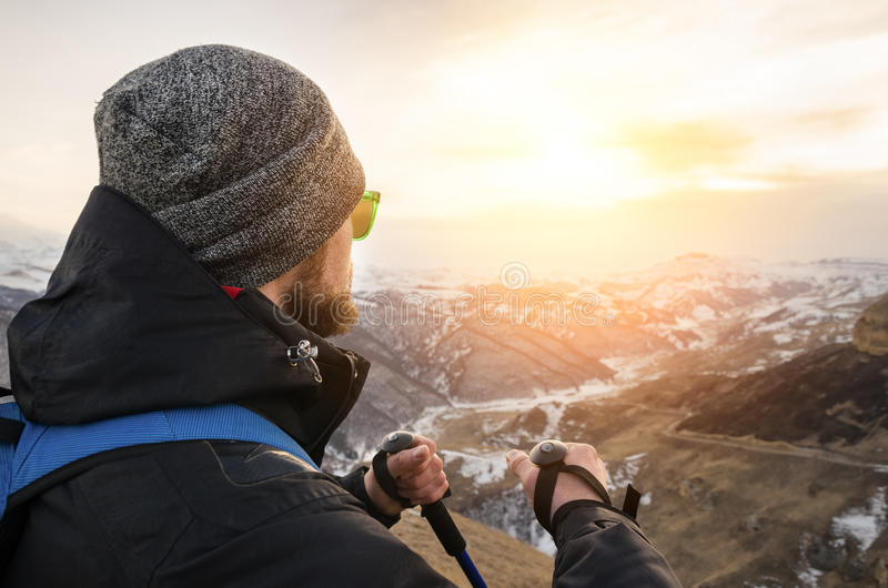 I giovani pantaloni a vita bassa barbuti che indossano un cappello e gli occhiali da sole con i bastoni da passeggio nordici e un immagini stock libere da diritti