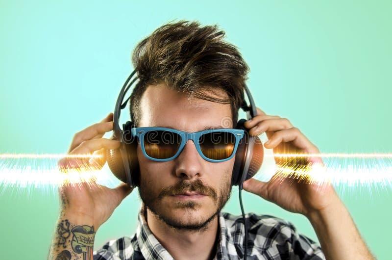 I giovani pantaloni a vita bassa hanno tatuato l'uomo, ascoltante la musica fotografia stock libera da diritti