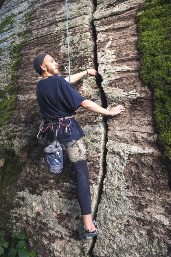 I giovani pantaloni a vita bassa sono impegnati in arrampicata con assicurazione sulle rocce con muschio verde fotografia stock