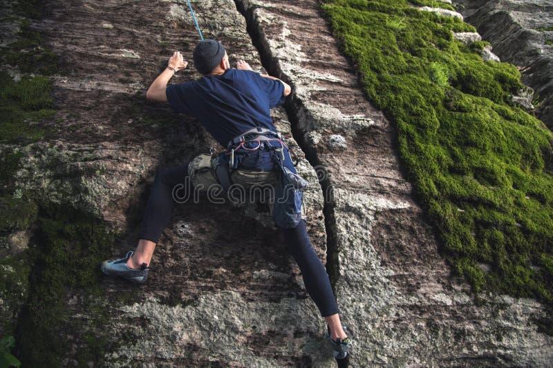 I giovani pantaloni a vita bassa sono impegnati in arrampicata con assicurazione sulle rocce con muschio verde immagini stock
