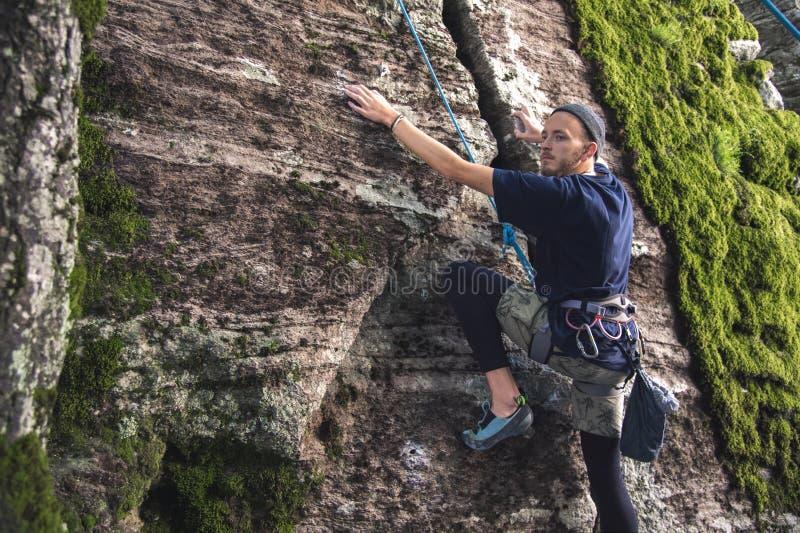 I giovani pantaloni a vita bassa sono impegnati in arrampicata con assicurazione sulle rocce con muschio verde immagini stock libere da diritti