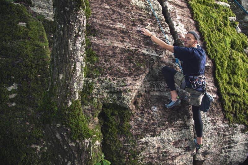I giovani pantaloni a vita bassa sono impegnati in arrampicata con assicurazione sulle rocce con muschio verde immagine stock