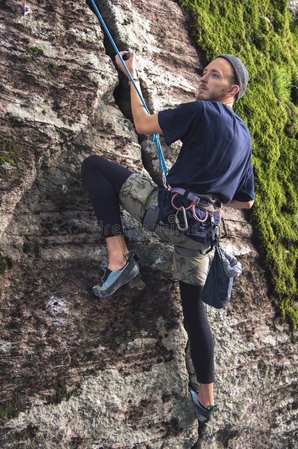 I giovani pantaloni a vita bassa sono impegnati in arrampicata con assicurazione sulle rocce con muschio verde immagine stock libera da diritti