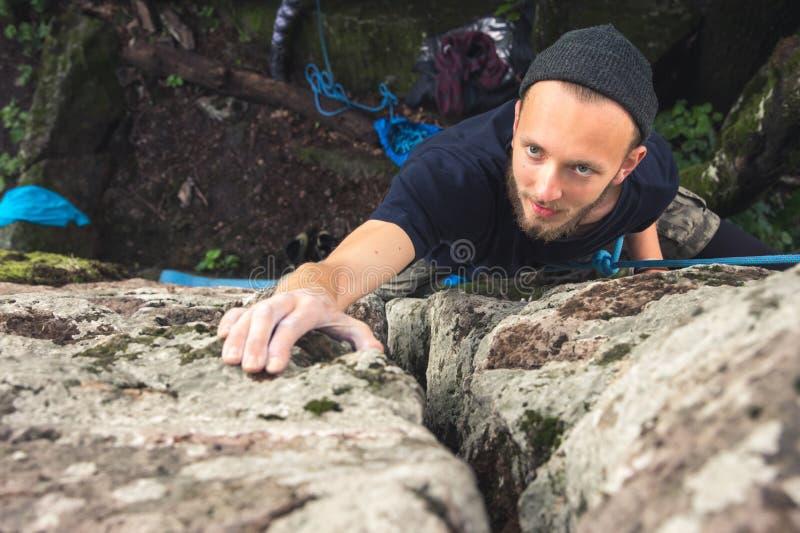 I giovani pantaloni a vita bassa sono impegnati in arrampicata con assicurazione sulle rocce con muschio verde fotografia stock libera da diritti