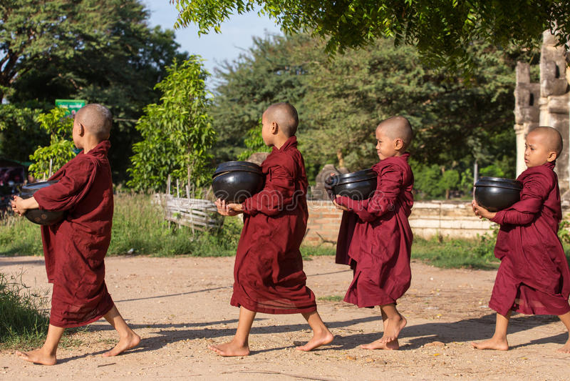 I giovani principianti buddisti camminano per raccogliere le elemosine e le offerti sulle vie di Bagan, Myanmar immagini stock