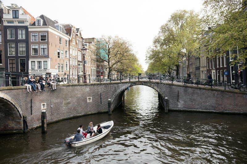 I giovani si siedono sul ponte sopra il canale di Amsterdam mentre piccola barca fotografia stock
