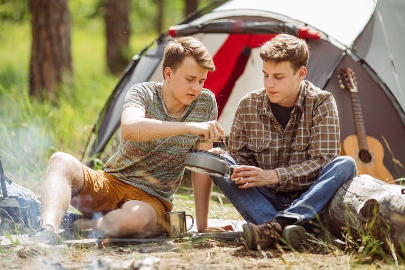 I giovani sono riscaldati in un fuoco ed in un cuoco fuori su una foresta dell'estate fotografie stock libere da diritti