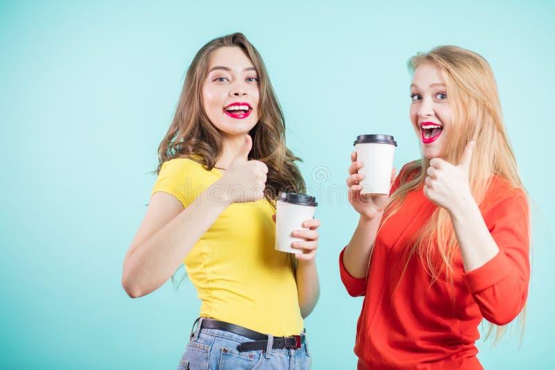 I giovani sorridenti felici due donne con dare delle tazze di caffè pollici aumentano il gesto fotografie stock libere da diritti