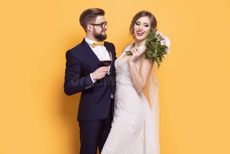 I giovani sorridenti recentemente hanno sposato su un fondo giallo immagine stock libera da diritti
