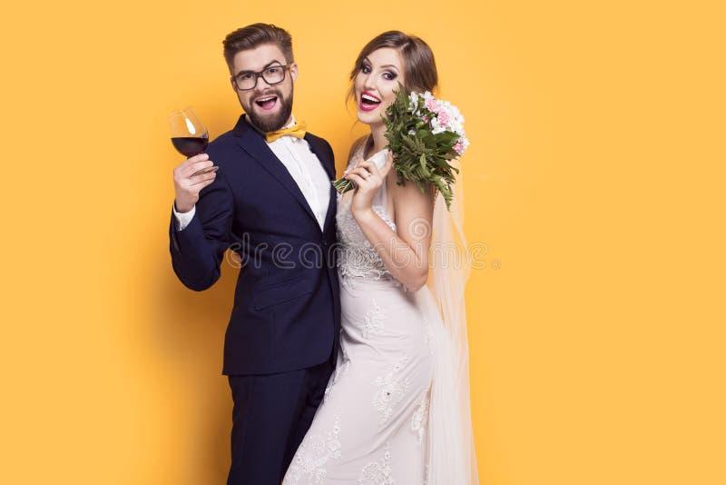 I giovani sorridenti recentemente hanno sposato su un fondo giallo fotografia stock libera da diritti