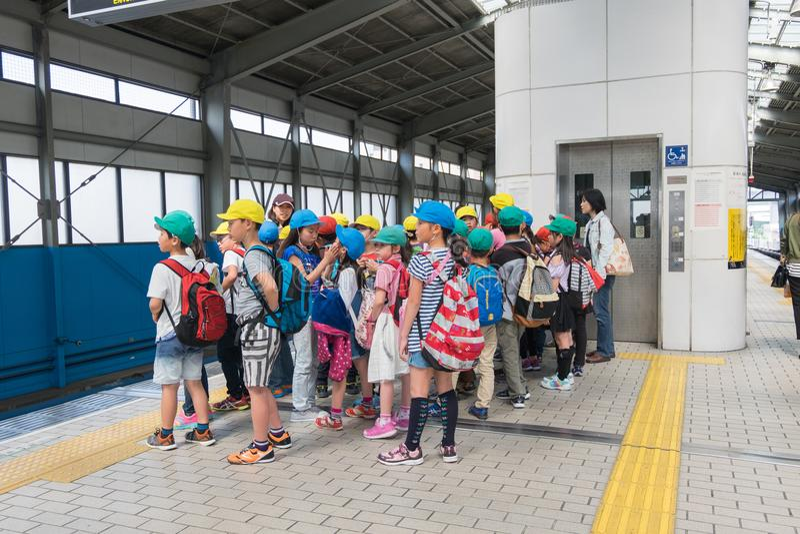I giovani studenti elementari giapponesi stanno avendo escursione in Osak immagini stock