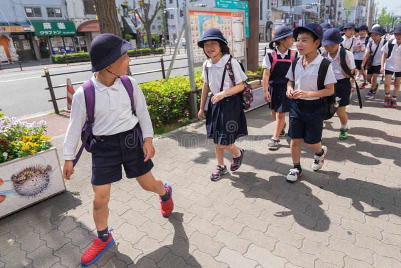I giovani studenti elementari giapponesi stanno avendo escursione in Osak immagine stock