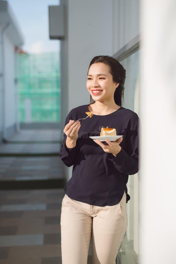 I giovani supporti felici della donna sul terrazzo dell'hotel con il piatto agglutinano di mattina La ragazza asiatica graziosa n fotografia stock