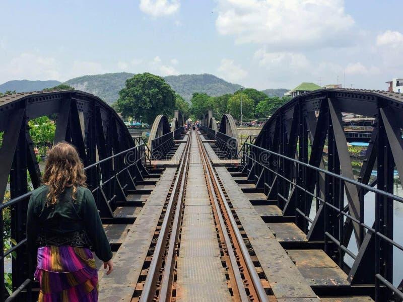 I giovani turisti femminili cammina lungo il ponte del fiume Kwai immagine stock libera da diritti