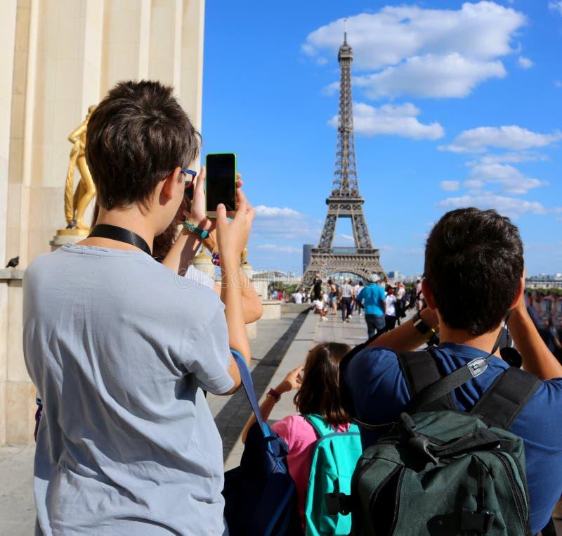I giovani turisti prendono le immagini della torre Eiffel a Parigi Francia immagine stock