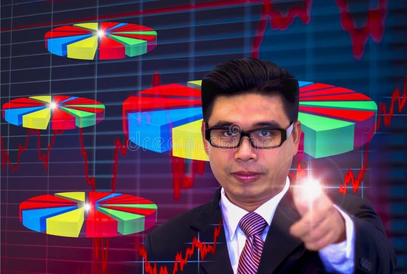 I giovani uomini d'affari asiatici, vetri scuri d'uso e vestiti neri, indicanti il grafico indicante delle dita, occhi sono comme immagini stock