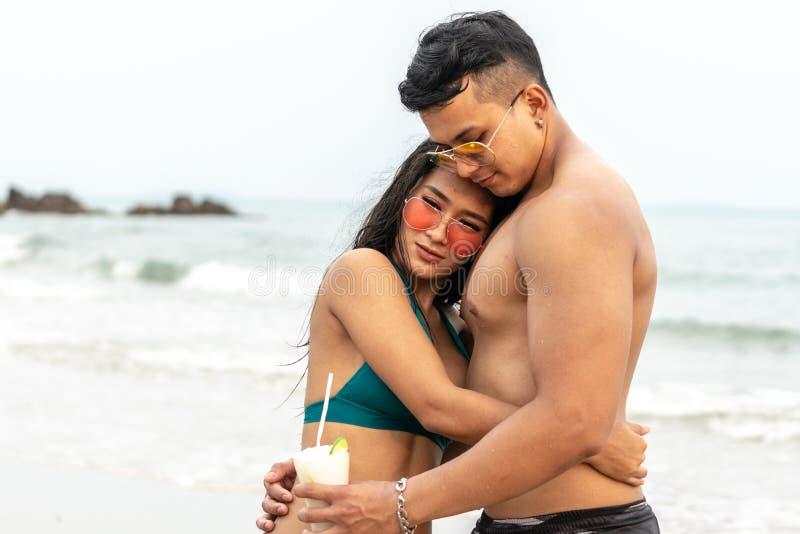 I giovani uomini tailandesi abbracciano con le ragazze tailandesi in un bikini verde messo felicemente dalla spiaggia immagini stock