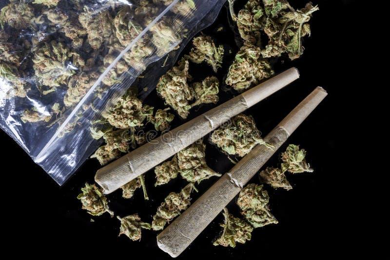 I giunti ed i germogli medici della cannabis hanno sparso dal nero del pacchetto qui sopra fotografia stock