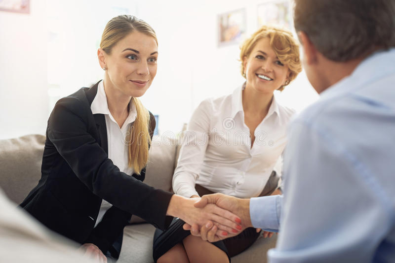 I am glad to work with you. Happy young businesswoman is greeting her business partner by handshake. They are sitting and smiling stock image