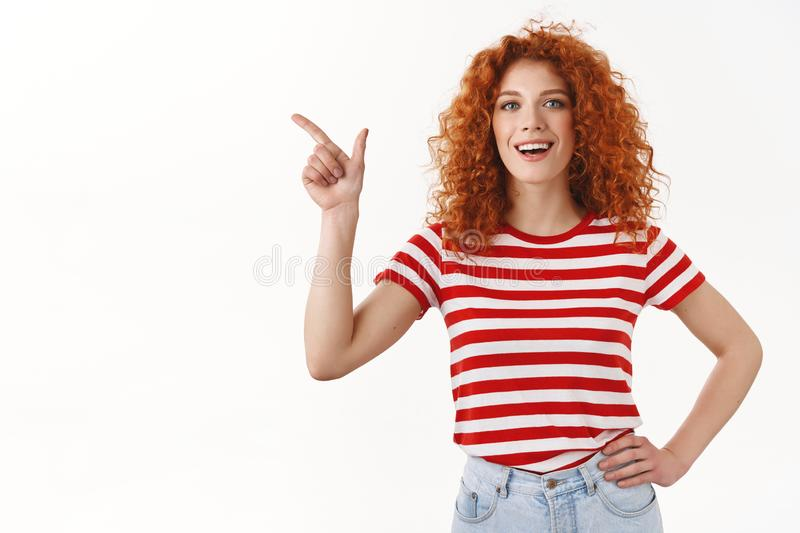 I got it. Attractive satisfied happy redhead curly european girl approve recommend good choice pointing upper left. Corner pleased smiling cheerful discuss royalty free stock images