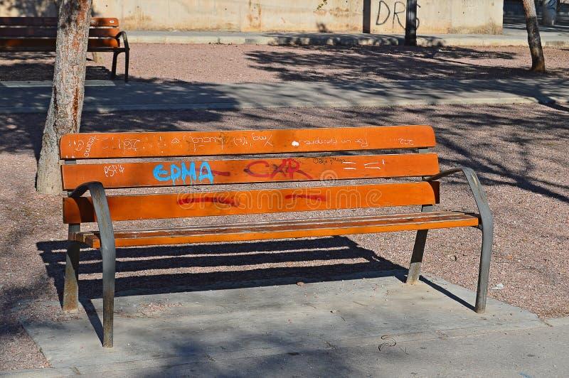 I graffiti hanno coperto il banco di parco fotografie stock
